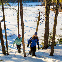 A woman and her daughter walk a trail near a beaver pond on Crommet Creek in the Society for the Protection of New Hampshire Forest's Dame Forest in Durham, New Hampshire. Winter.