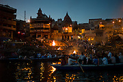 Tourists watch body bathed in River Ganges and Hindu funeral pyre cremation at Manikarnika Ghat, Holy City of Varanasi, India