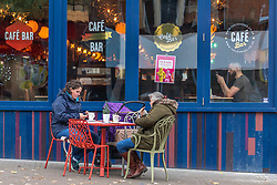 © Licensed to London News Pictures. 02/12/2020. London, UK. Two tiers shoppers have a tea break at a cafe in Sutton. Shoppers are out in force in Sutton, South West London on the first day of the new tiered system as shops have been given the the green light to say open 24 hours a day for the Christmas period. The Government has announced the end of lockdown and introduced a new 3-tiered system for England, which came into effect this morning (Wednesday 2nd December). All non-essential shops, restaurants, gyms, pubs if serving food and golf courses are allowed to reopen again. Photo credit: Alex Lentati/LNP