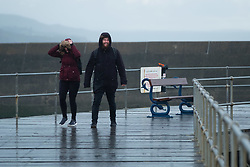 © Licensed to London News Pictures<br /> Aberystwyth, UK. 26/10/2018. A couple walk along the harbour jetty as bitterly cold northerly winds blow over Aberystwyth on the Cardigan Bay coast of west Wales as the weather turns decidedly wintry.  photo credit Keith Morris/ LNP
