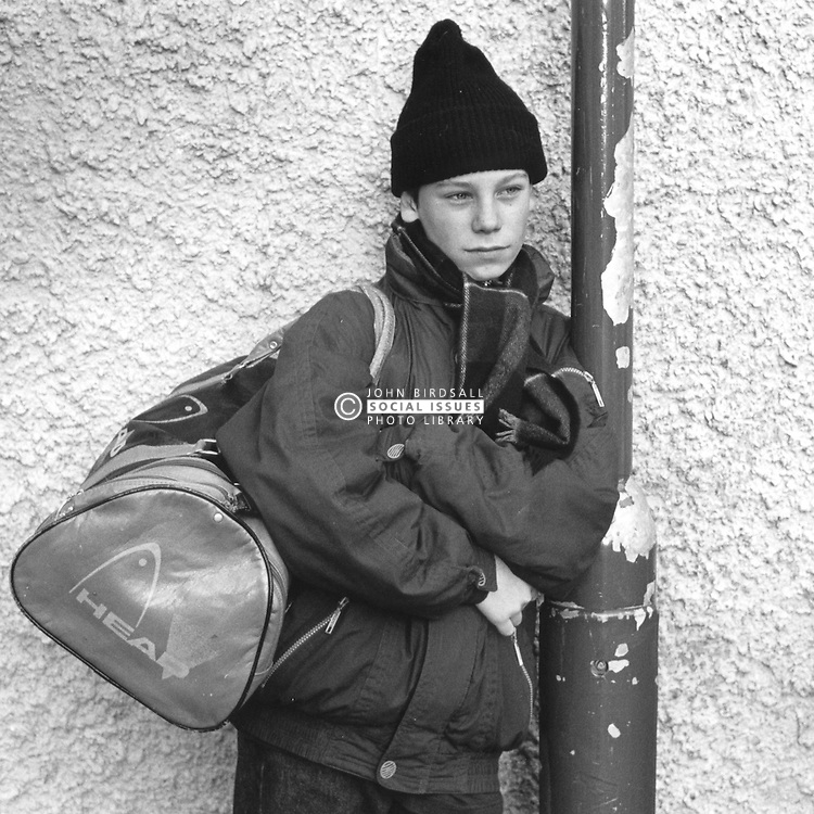 Teenage boy standing in street carrying bag and leaning against lamp post looking serious,