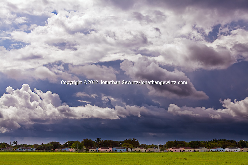 A dramatic sky of dark rain clouds contrasts with colorful houses and green fields near Ingraham Highway in Homestead, Florida. WATERMARKS WILL NOT APPEAR ON PRINTS OR LICENSED IMAGES.