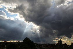 © Licensed to London News Pictures. 17/08/2020. London, UK. Crepuscular rays (also called sun rays and sunbeams)  through thunderclouds, over north London. When sunlight shines through gaps in clouds and continues through an atmosphere that contains dust and/or haze is known as Crepuscular rays. Photo credit: Dinendra Haria/LNP