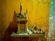 """24 FEBRUARY 2015 - PHNOM PENH, CAMBODIA: A """"spirit house"""" in front of an apartment in the White Building. The White Building, the first modern apartment building in Phnom Penh, originally had 468 apartments, and was opened the early 1960s. The project was overseen by Vann Molyvann, the first Cambodian architect educated in France. The building was abandoned during the Khmer Rouge occupation. After the Khmer Rouge were expelled from Phnom Penh in 1979, artists and dancers moved into the White Building. Now about 2,500 people, mostly urban and working poor, live in the building. Ownership of the building is in dispute. No single entity owns the building, some units are owned by their occupants, others units are owned by companies who lease out apartments. Many of the original apartments have been subdivided since the building opened and serve as homes to two or three families. The building has not been renovated since the early 1970s and is in disrepair. Phnom Penh officials have tried to evict the tenants and demolish the building but residents refuse to move out.   PHOTO BY JACK KURTZ"""
