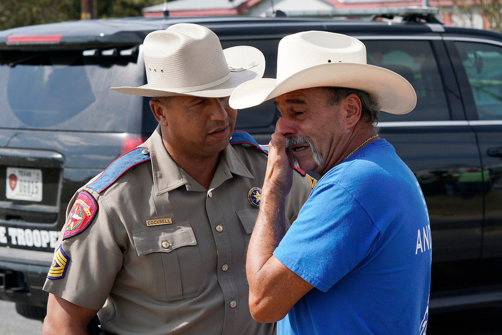Texas DPS Sgt. Deon Cockrell (L) comforts Rene Moreno outside the site of the shooting at the First Baptist Church of Sutherland Springs, Texas, U.S. November 7, 2017.  REUTERS/Rick Wilking