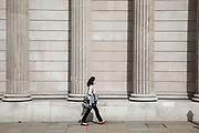 People wearing face masks pass the columns of the Bank of England in the City of London financial district which is still very quiet with few people around and working due to the Coronavirus outbreak as lockdown continues on 9th September 2020 in London, United Kingdom.