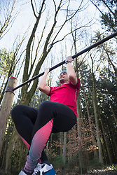 Mature man doing chin-ups on horizontal bar in forest