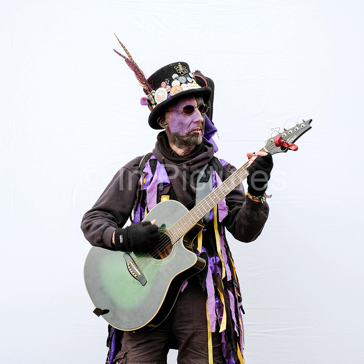 Portrait of a Rackaback Morris musician wearing traditional costume at an orchard-visiting wassail at Sledmere House in the Yorkshire Wolds, United Kingdom on 20th January 2018. Wassail is a traditional Pagan winter celebration in cider-producing regions of England, reciting incantations and singing to the trees to promote a good harvest for the coming year. Pieces of toast soaked in cider are hung in the branches to attract robins to the tree as these are said to be the good spirits of the orchard. To ward off evil spirits, villagers scare them away by banging pots and pans and making as much noise as possible