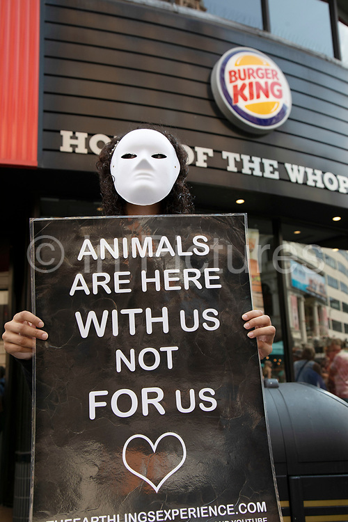 Animal rights demonstrator holds up a placard suggesting we should live with animals not kill them for food, protests outside Burger King in central London, United Kingdom.