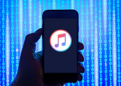 Person holding smart phone with Apple Music  logo displayed on the screen. EDITORIAL USE ONLY