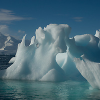 A weathered iceberg drifts in the Neumayer Channel near the Antarctic Peninsula, Antarctica. Background mountains are on Anvers Island.
