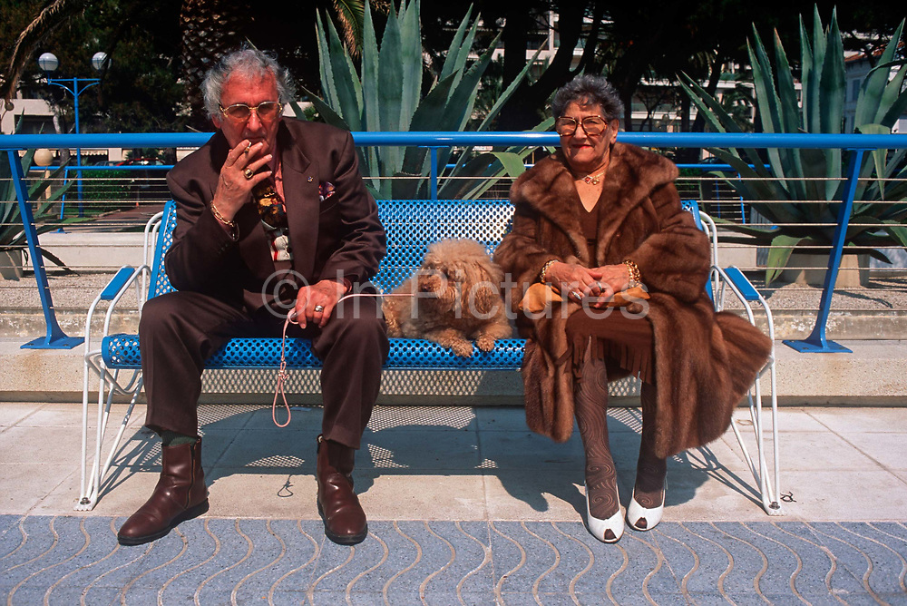 A typical elderly 1990s French couple from the Cote dAzur sit on a bench of their seafront with their pet poodle, on 10th May 1996, in Juan-les-Pins, France.