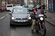 Motorcycle courier with the word BLOOD on his screen in London, England, United Kingdom. Medical couriers transport blood, organs and other medical requirements between hospitals and for patient needs. Healthcare Transport is the systematic process by which patient critical materials, such as patient specimens, pharmaceuticals, supplies and medical records are transported to and from multiple points within healthcare organizations.