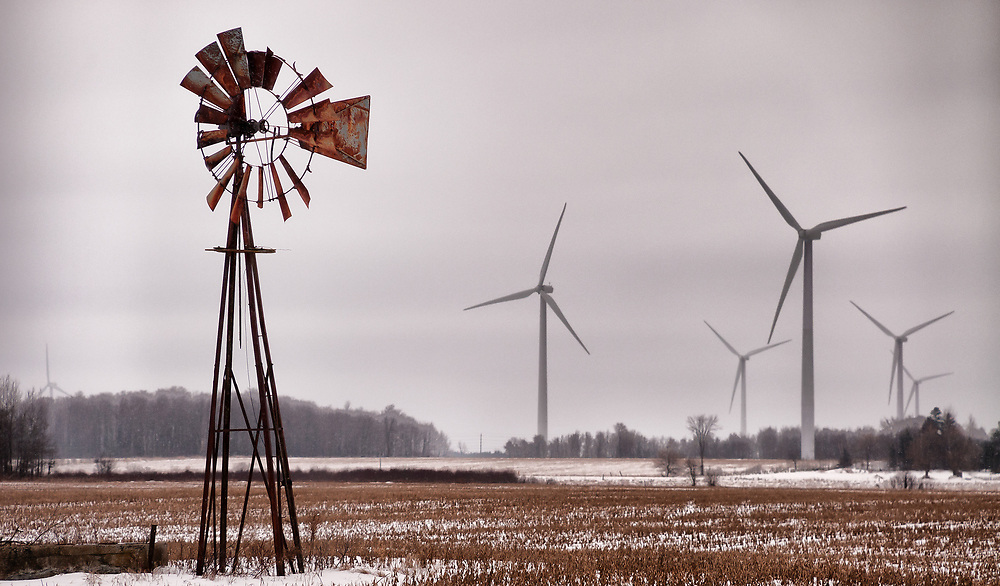 A farm windmill, an icon of the rural landscape stands decrepit and neglected as the new age monsters march in.