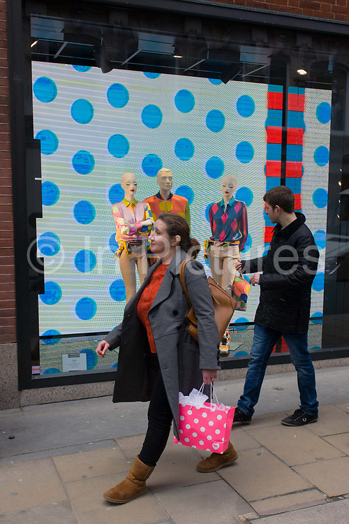 A woman consumer carrying a spotty shopping bag passes a window theme of dots in the window of Etro on Old Bond Street, central London. Walking past the display of three mannequins wearing stylish clothing is a coincidental scene, a humerous moment in the life of this exclusive street in the capital known for fine couture and jewellery of luxury brands. The background is a video playing on a continuous loop alternately featuring spots and stripes.