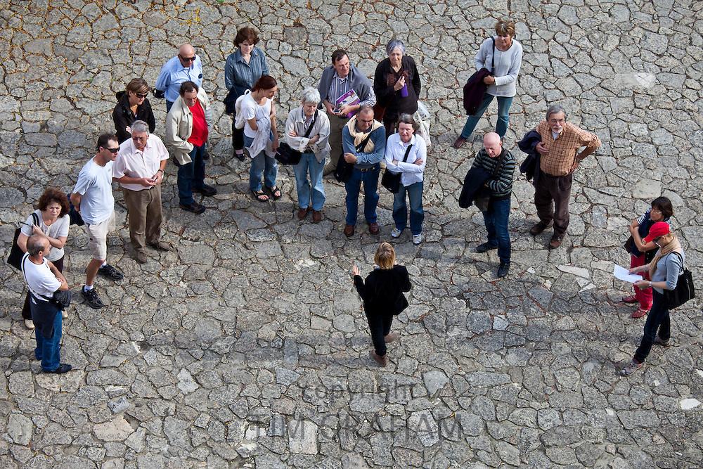 Tourists listen to tour guide in quaint street in St Emilion, Bordeaux, France