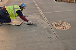 Worker smoothing concrete sidewalk pour as part of the Construction of Central Connecticut State University New Academic and Office Building. Project No: BI-RC-324. Architect: Burt Hill Kosar Rittelmann Associates. Contractor: Gilbane Building Company, Glastonbury, CT.