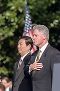 US President Bill Clinton and Chinese Premier Zhu Rongji stand at attention during a state arrival ceremony at the White House April 8, 1999 in Washington, DC.