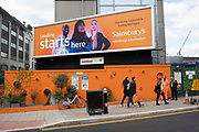 Orange colour scene including a hoarding, Sainsburys supermarket billboard, overalls and bike wheels in London, England, United Kingdom.