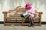 © Licensed to London News Pictures. 18/06/2014. Ascot, UK. A woman reads a newspaper int he sunshine.  Day two at Royal Ascot 18th June 2014. Royal Ascot has established itself as a national institution and the centrepiece of the British social calendar as well as being a stage for the best racehorses in the world. Photo credit : Stephen Simpson/LNP
