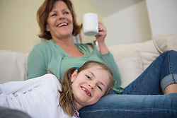 Grandmother and granddaughter on couch in living room, smiling