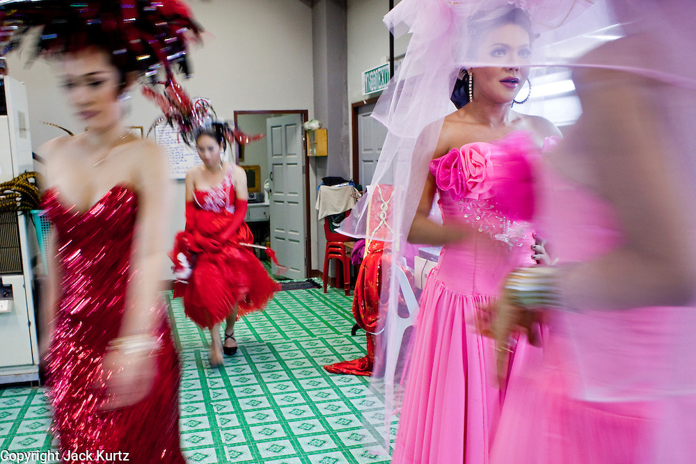 "Oct. 7, 2009 -- BANGKOK, THAILAND:  ""Ladyboys"" wait to go on stage while the performers from the first act leave the stage during the performance at the Mambo Cabaret in Bangkok, Thailand. The performers at the Mambo Cabaret in Bangkok, Thailand are all ""Ladyboys,"" or kathoeys in Thai. Recognized as a third gender, between male and female, they are born biologically male but live their lives as women. Many kathoey realize they are third gender in their early teens, some only as old 12 or 13. Kathoeys frequently undergo gender reassignment surgery to become women. Being a kathoey in Thailand does not carry the same negative connotation that being a transgendered person in the West does. A number of prominent Thai entertainers are kathoeys. Photo by Jack Kurtz / ZUMA Press"