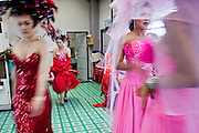 """Oct. 7, 2009 -- BANGKOK, THAILAND:  """"Ladyboys"""" wait to go on stage while the performers from the first act leave the stage during the performance at the Mambo Cabaret in Bangkok, Thailand. The performers at the Mambo Cabaret in Bangkok, Thailand are all """"Ladyboys,"""" or kathoeys in Thai. Recognized as a third gender, between male and female, they are born biologically male but live their lives as women. Many kathoey realize they are third gender in their early teens, some only as old 12 or 13. Kathoeys frequently undergo gender reassignment surgery to become women. Being a kathoey in Thailand does not carry the same negative connotation that being a transgendered person in the West does. A number of prominent Thai entertainers are kathoeys. Photo by Jack Kurtz / ZUMA Press"""