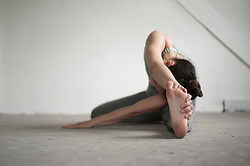 Mid adult woman practicing janu sirsasana pose in yoga studio, Munich, Bavaria, Germany