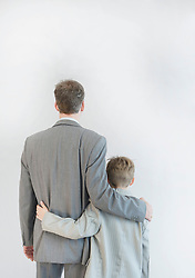 Father and son walking arm in arm against white background