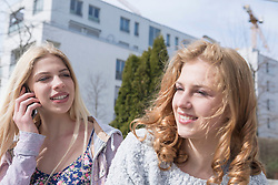 Teenage girl with her friend talking on mobile phone, Munich, Bavaria, Germany