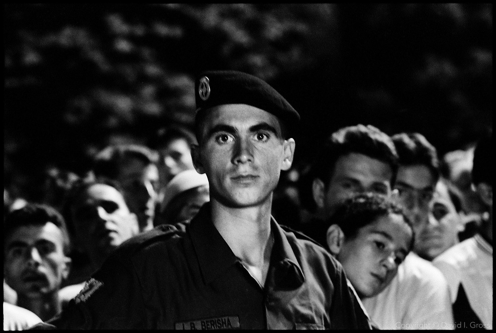A member of the Kosovo Protection Corps, the successors to the Kosovo Liberation Army (KLA), joins a small crowd celebrating the liberation of Kosovo from the Serb military (as ethnic Albanians see it), in Prizren, Kosovo. The party emphasized the role of the KLA, and there was no mention of NATO's role in pushing the Serbs out.