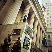 The Monday morning following the attacks on the World Trade Center on September 11th we see members of the National Guard wearing dust masks standing beneath the high columns of the Federal Hall, located at 26 Wall Street in New York City. It was the first capitol of the United States of America and the site of George Washington's first inauguration in 1789. It is also the place where the United States Bill of Rights was passed. To celebrate the near-return to financial normality, New Yorkers' spirit was proved intact by the hanging of US flags from buildings. Days after the historical events, security was prominent at all nationally symbolic institutions and buildings. As a show of force, it was also a clear deterrent for would-be criminals when New Yorkers felt vulnerable to further attack.