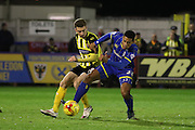 Lyle Taylor of AFC Wimbledon and Jack Connors of Dagenham & Redbridge during the Sky Bet League 2 match between AFC Wimbledon and Dagenham and Redbridge at the Cherry Red Records Stadium, Kingston, England on 24 November 2015. Photo by Stuart Butcher.