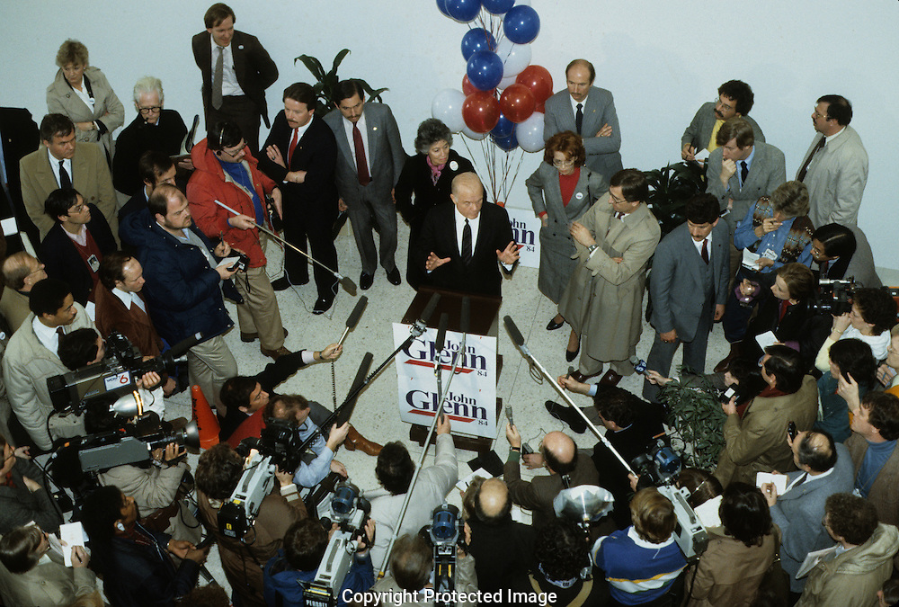 John Glenn at a press briefing in Iowa--A perfect illustration of candidate, candidate's wife, Secret Service, handlers and press all doing their jobs.  ..Photograph by Dennis Brack b23