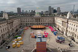 © Licensed to London News Pictures. 14/07/2021. London, UK. Somerset House  unveils Dodge, a contemporary funfair in the centre of its historic courtyard this Summer. At centre of this spectacular open-air space, joyfully transformed by designer Yinka Ilori, sits a buzzy bumper car track complete with artful dodgems. As riders race around thecourse, they collectivelycontrolthe performance of a new musicalcomposition, written by award winning Somerset House Studios artistAnna Meredith, who has teamed up with fellow Studios resident and Bafta-winning sound artistNick Ryan. Photo credit: Ray Tang/LNP