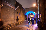Night scene in London on a cold winter evening in Borough, London. The railway bridge arches in this area are lit blue.