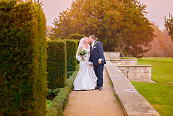 Bride and groom sharing a kiss in the grounds at Ashridge House