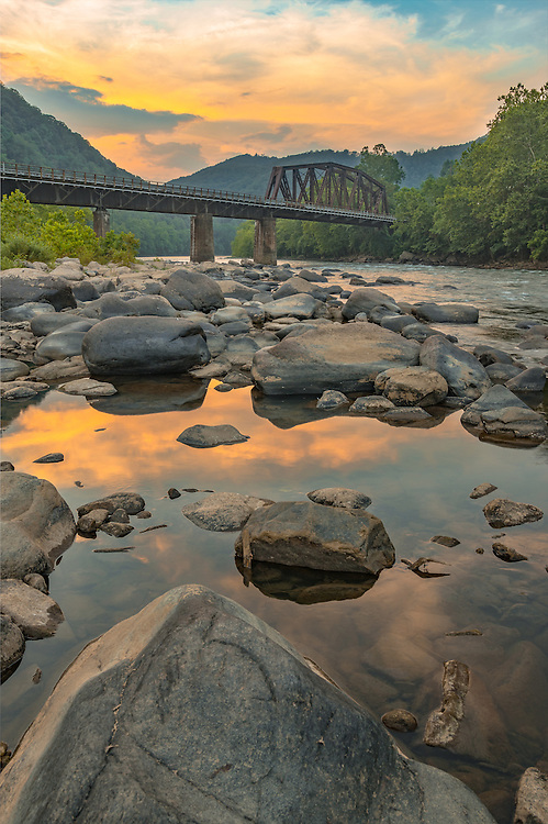 Sunsetting over the rail bridge in Thurmond, West Virginia. Viewed from the rocky banks of the New River.