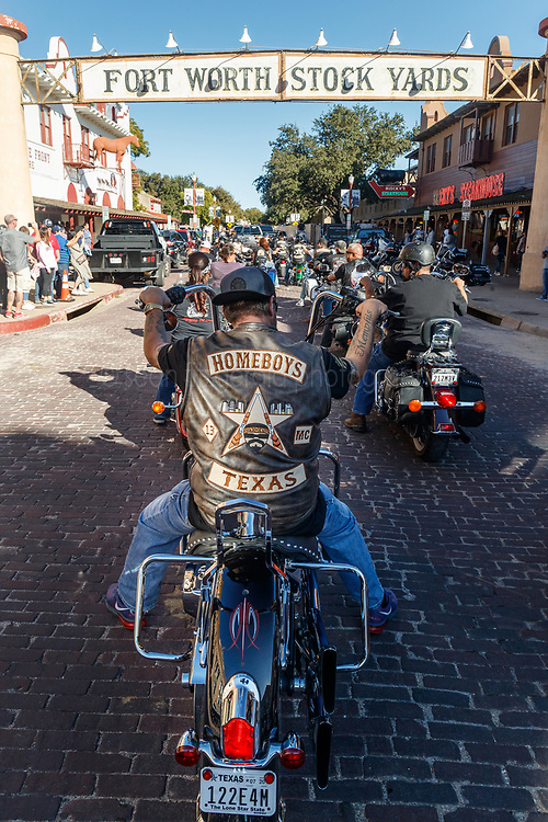"""""""Homeboys"""" motorcycle club ride beneath Fort Worth Stockyards sign, Fort Worth Texas, USA."""