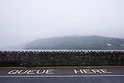 A Quueue Here sign on the road at the Corran Ferry crossing  on Inverscaddle Bay, Ardgour, Scotland.