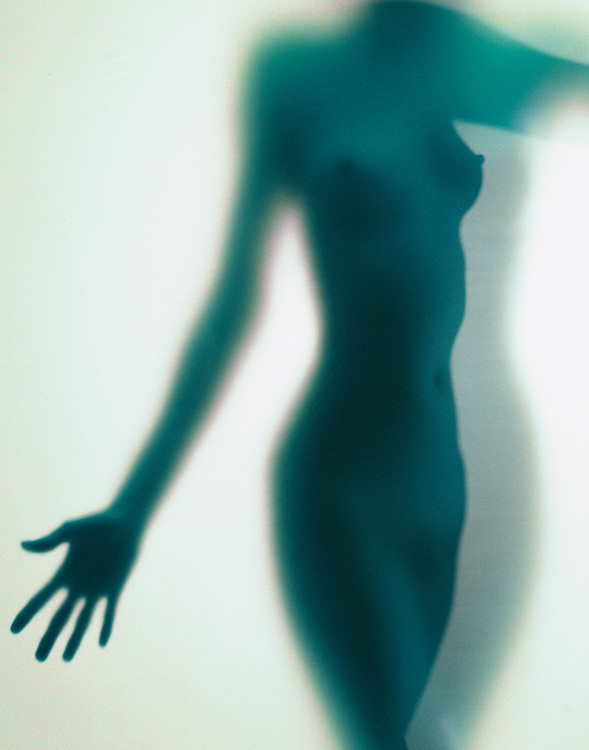 Graceful nude woman in silhouette with shadows behind translucent green matte material