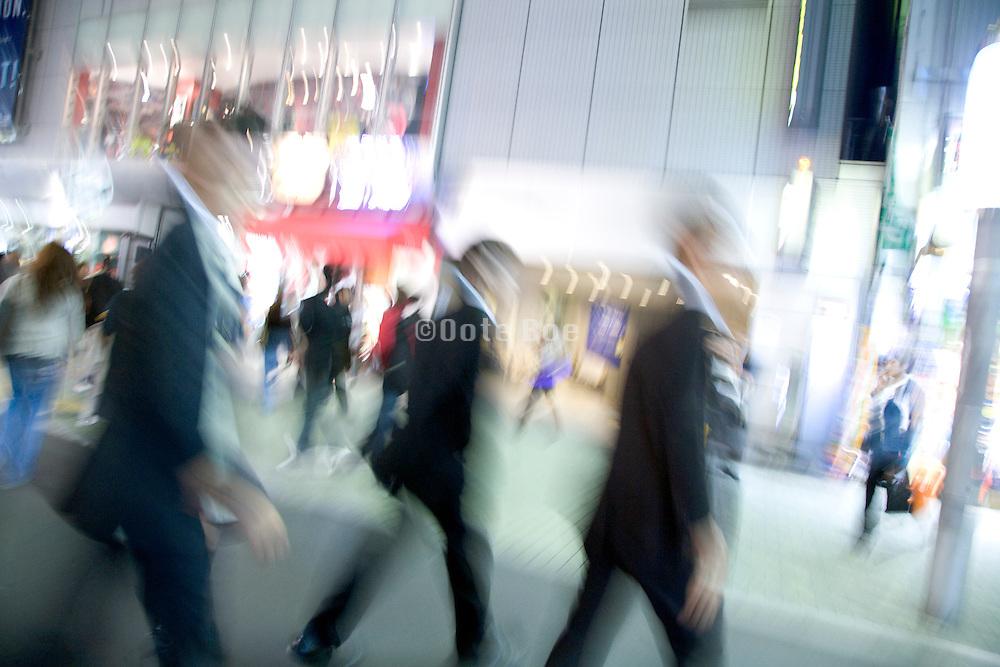 blurry view of businessmen walking through Tokyo at night