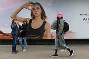 Visitors to the capital take a photo with a smartphone as an Islamic man with two rucksack walks past a billboard ad featuring the face of a model advertising a perfume outside the retailer Debenhams on Oxford Street, on 16th April 2018, in London, England.
