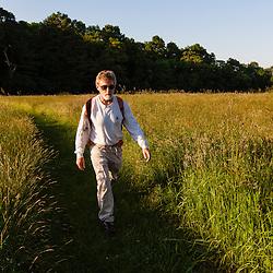 A man walks through the hay field at Phillips Farm in Marshfield, Massachusetts.