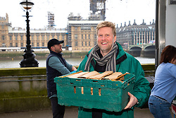 EDITORIAL USE ONLY Darren Henaghan, Managing Director at Borough Market, helps unload some of a thousand fruit and vegetable packages outside St Thomas' Hospital, which are destined for healthcare workers fighting the COVID-19 pandemic as Borough Market spearheads the national 'Feed The Frontline' campaign, London.