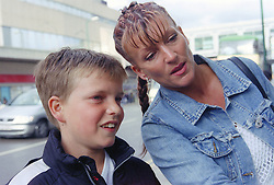 Single mother with young son looking at shop window display in town centre,