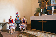 Heimat & Brauchtum Series: Johannisreiten in Casel, Brandenburg, with Marcel as the Johannis.<br /> <br /> Sorbian girls in traditional costume are sewing the 'Johann' into a floral dress of blue cornflowers. Sorbian women are weaving rushes into a crown adorned with bouquets of different flowers.<br /> The rushes along with water lilies have been picked by a group of young men in the early morning hours. At around 5am they went deep into the woods, wading through ponds to pick the best plants.<br /> <br /> The crown always has cornflowers, rushes, roses and water lilies because of its specific healing effects. Legend has it, if they are picked on this specific day of the Nativity of Saint John the Baptist on June 24th (Johannistag related to Johannis der Täufer), the effects of the flowers are even stronger.<br /> <br /> The Johannis has to ride on his horse, people of the village have to pull him off of his horse, stealing his crown and picking his cornflowers from his suit.<br /> <br /> This Sorbian tradition has its origins many hundreds of years ago. It was first mentioned on a written record from 1880 with pointing out, that this tradition has been celebrated since many generations when people still worshiped Germanian Gods and the Wenden and Sorbian people settled in this area. <br /> With the Christianization, this pagan tradition has been linked to John the Baptist.  <br /> <br /> Since after the war 1945/46 the Johannisreiten has been celebrated every year, even through the suppression of the Sorbian Minority in times of the DDR.<br /> The tradition survived only in Case, because after the war, there were not enough men left in other villages.