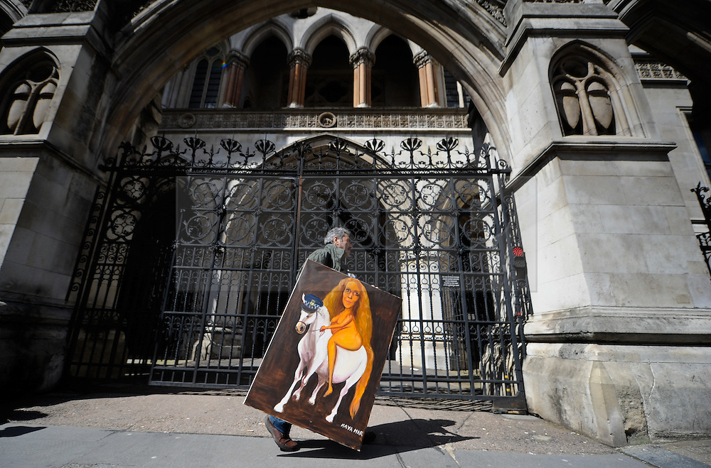 © Licensed to London News Pictures. 11/05/2012.London, Britain. Political satire artist Kaya Mar carries his painting of Rebekah Brooks outside the Leveson Inquiry at the High Court.Brooks will give evidence at the Leveson Inquiry into press ethics, over a row about phone-hacking by a NoW journalist.Photo credit : Thomas Campean/LNP