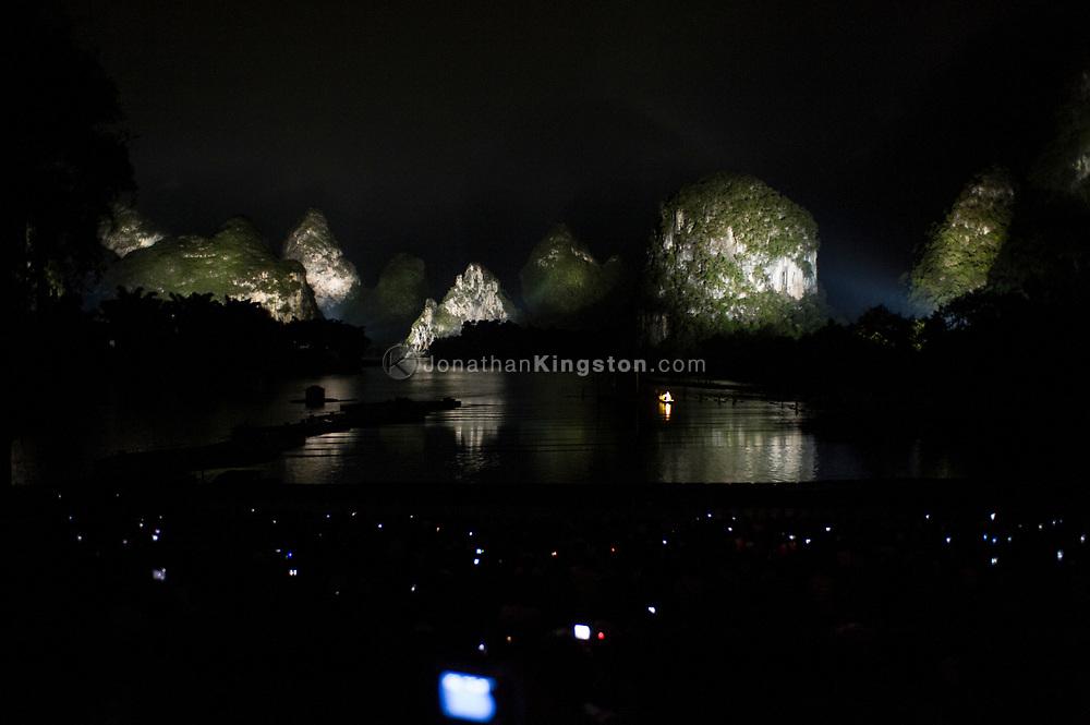 Digital camera backs betray audience members watching the Liu Sanjie light show, The Impression, in Yangshuo, China.