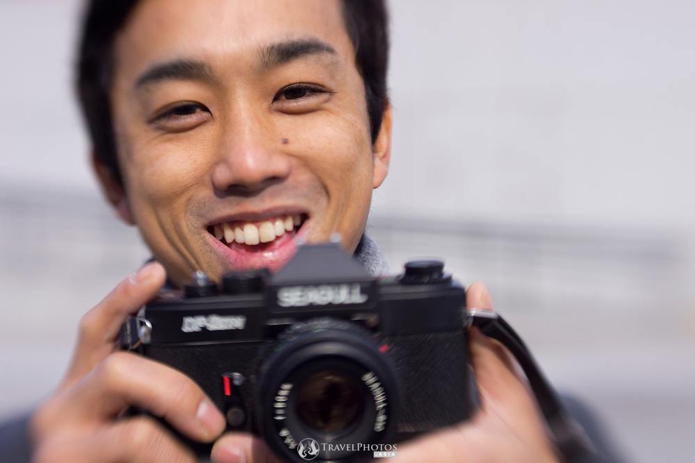 A Japanese man poses with an old Seagull SLR film camera in the 175th year of photography.